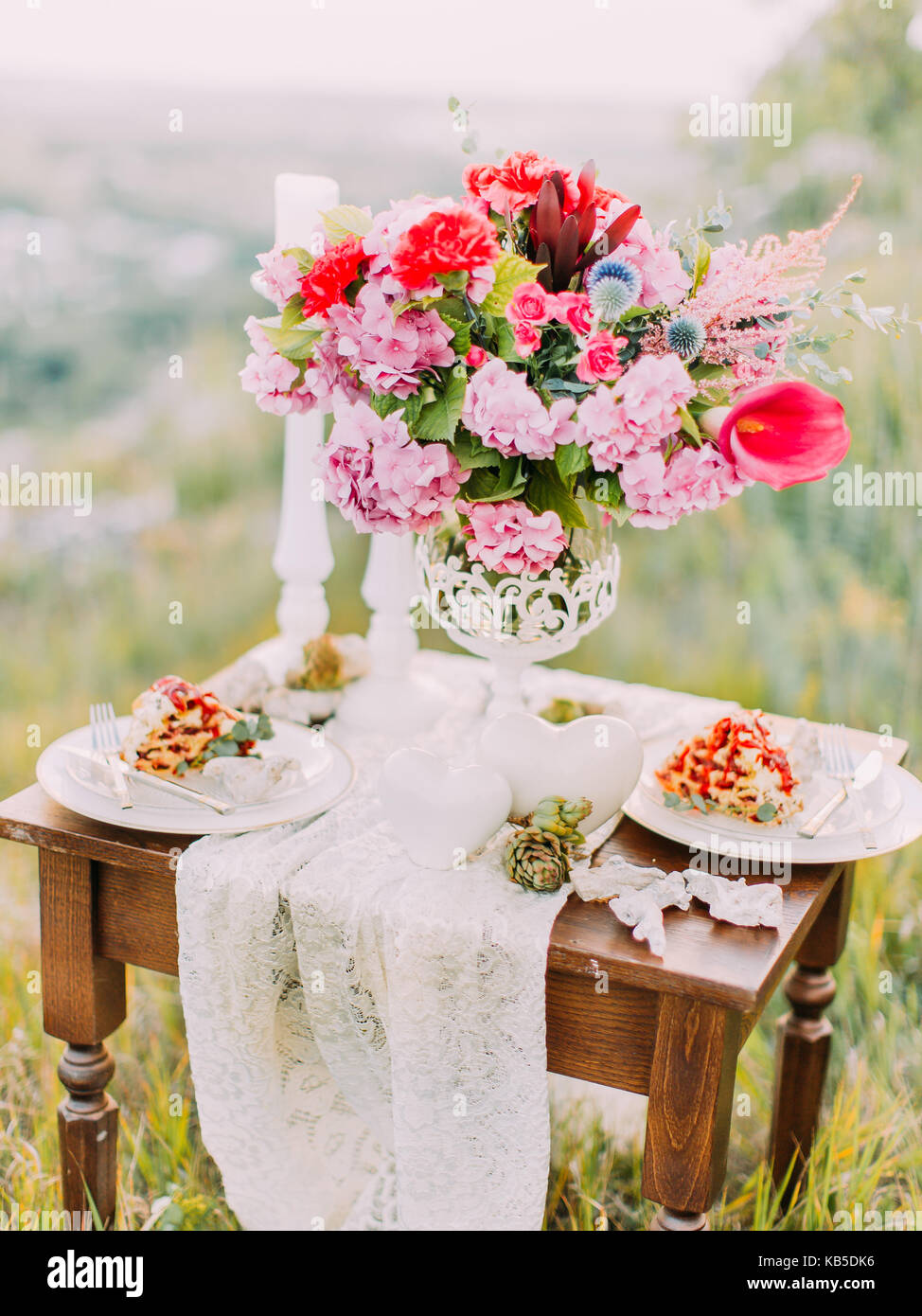 The vertical view of the wedding table set consisted of the bouquet the vertical view of the wedding table set consisted of the bouquet of flowers cake and candles in the mountains izmirmasajfo