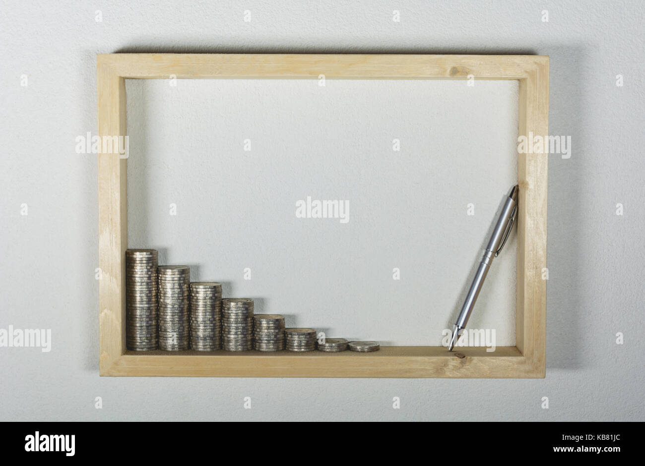stack coin with pen in wooden frame on white wall background Stock ...