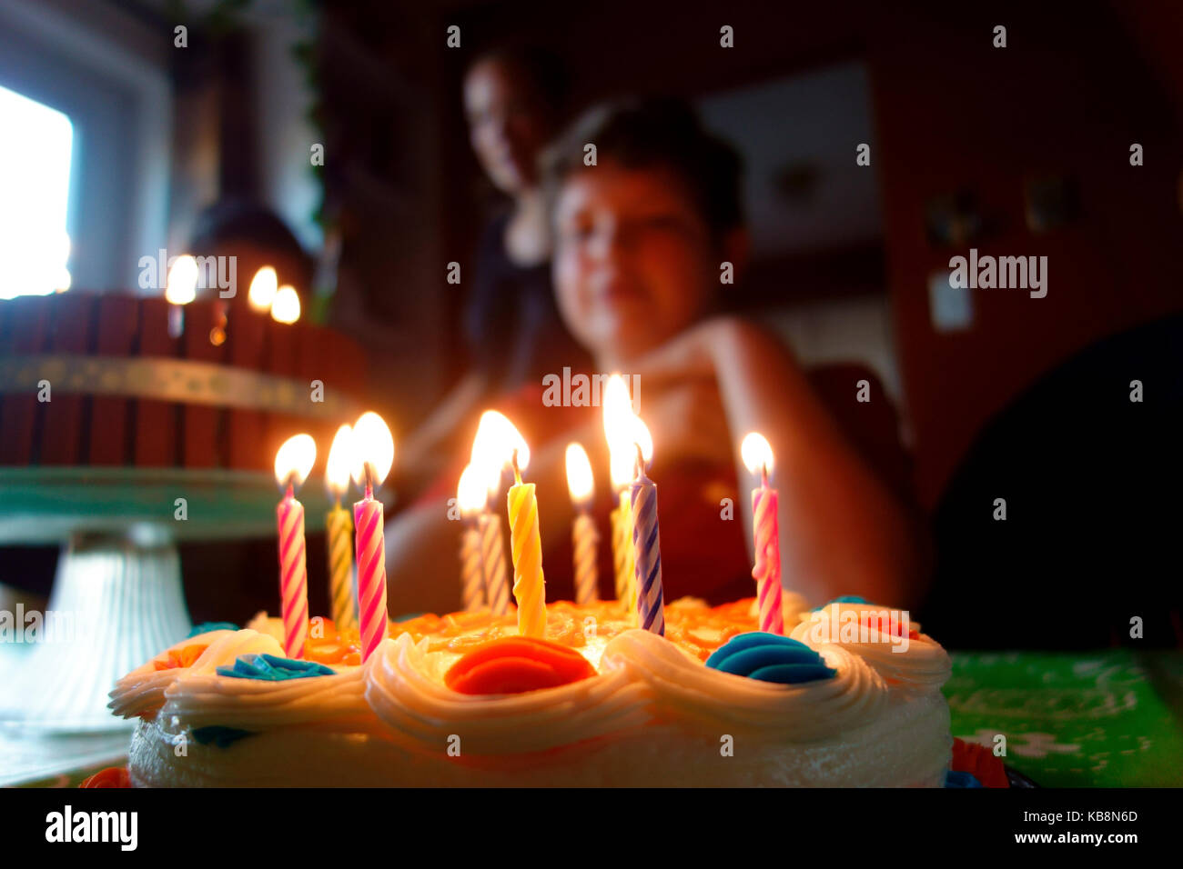 A Birthday Cake With Lit Candles In Front Of An 11 Year Old Boy