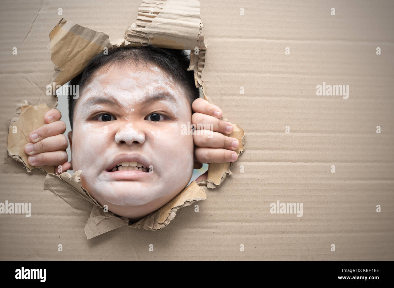 ghost kid angry and looking through hole on cardboard halloween day concept copy space