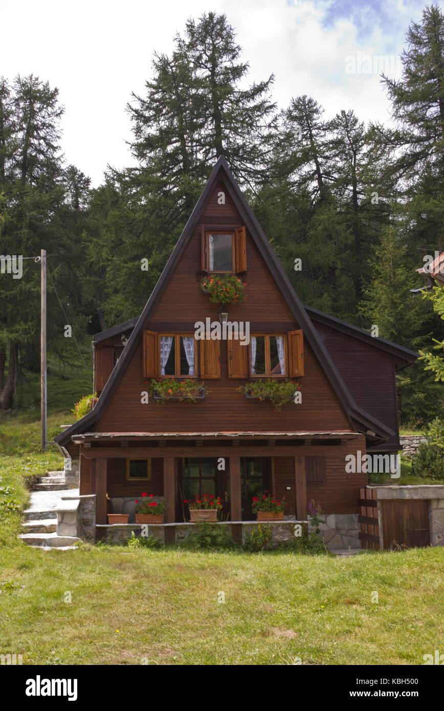 MADESIMO, ITALY   AUG 18 2014: Traditional Mountain Chalet In The Summer  Season, With A Strong Slope Roof, Isolated Through Trees
