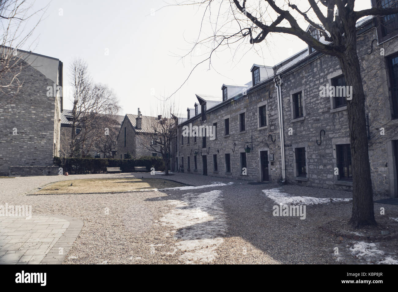 Stone building frames the outsides of a small park in Montreal Stock ...