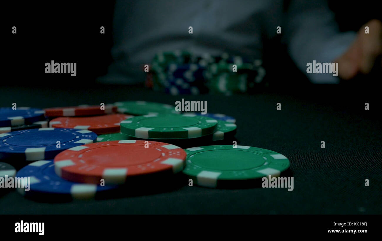 Close-up of hand with throwing gambling chips on black background. Poker player increasing his stakes throwing tokens onto the gaming table. & Close-Up of Man Throwing a Poker Chips in slow motion. Close-up of ...