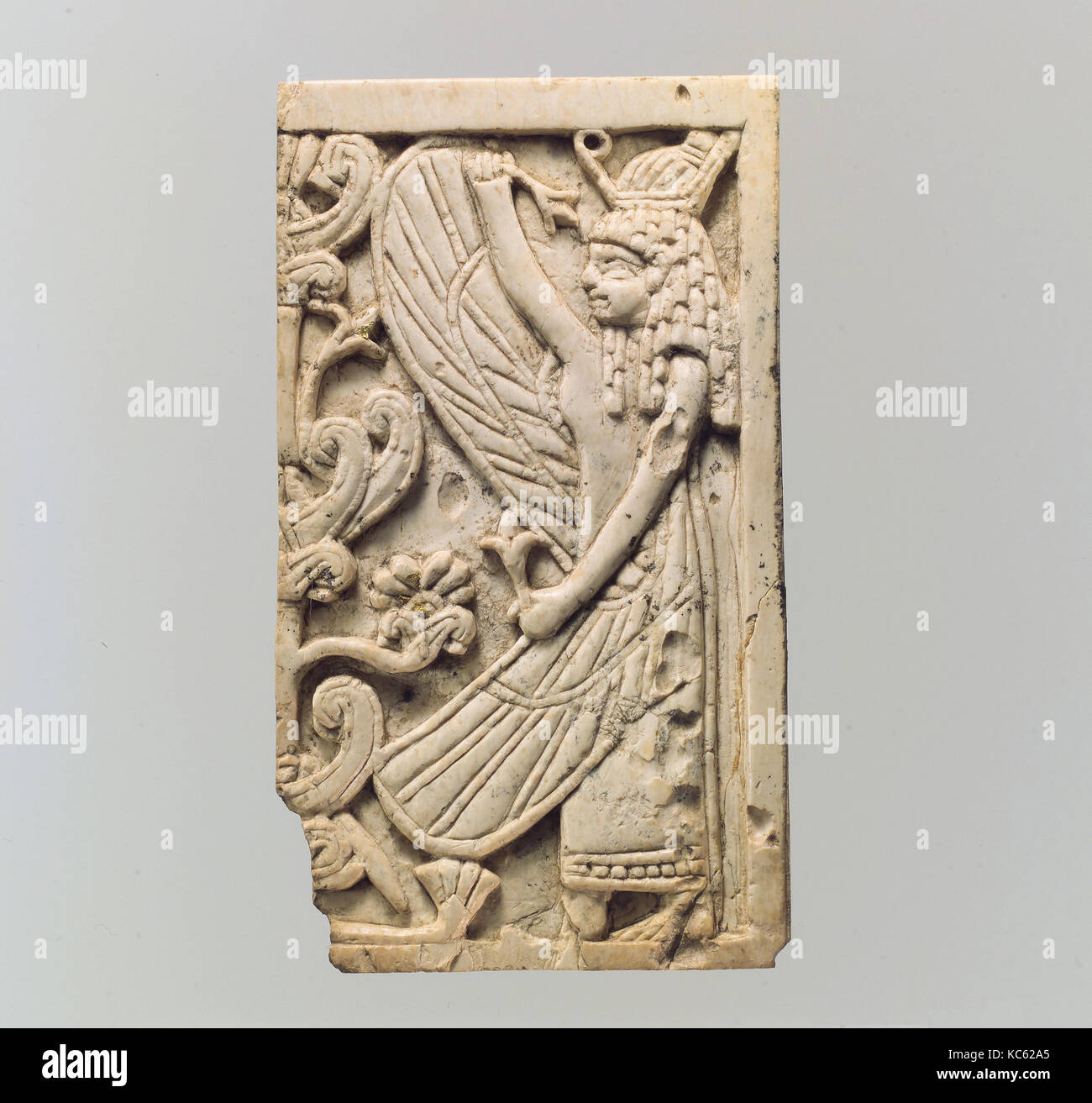 Furniture plaque carved in relief with a winged female figure and