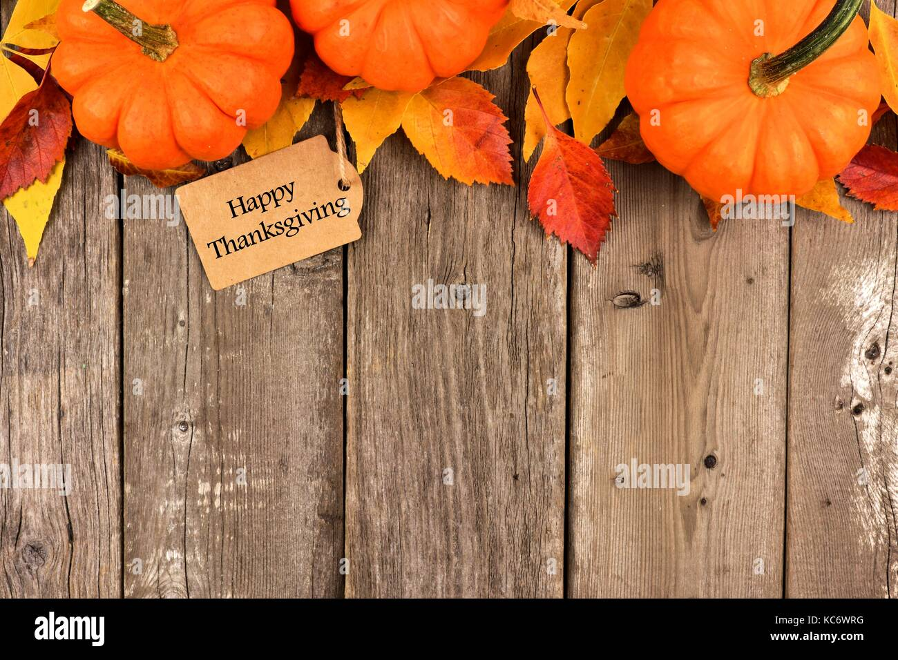Happy Thanksgiving Gift Tag With Top Border Of Pumpkins And Autumn Leaves Over A Rustic Wood Background