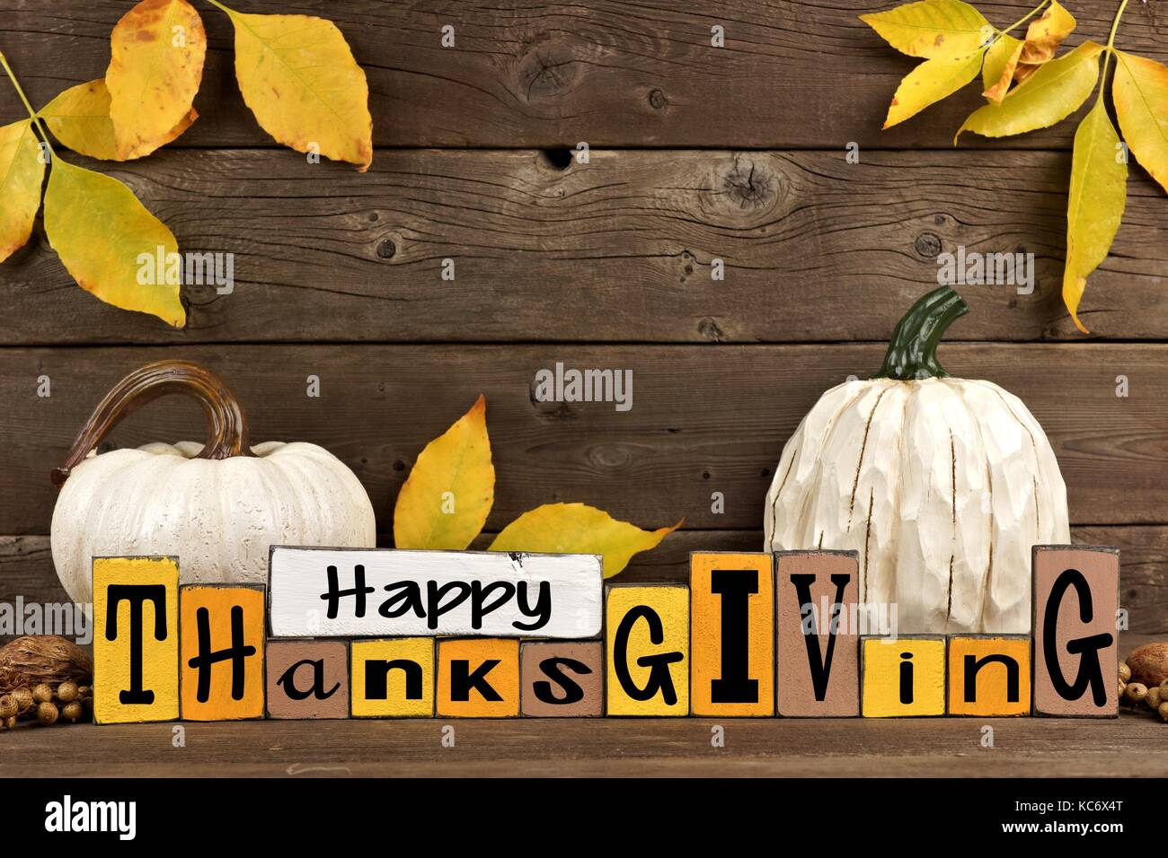 Happy Thanksgiving Wood Sign With White Pumpkins And Leaves Against A Rustic Wooden Background