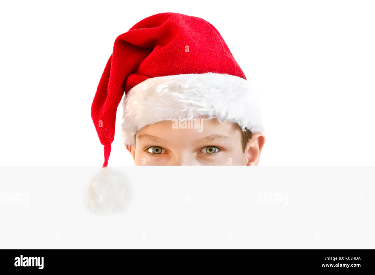 young boy in red santa hat hiding behind a blank paper stock photo