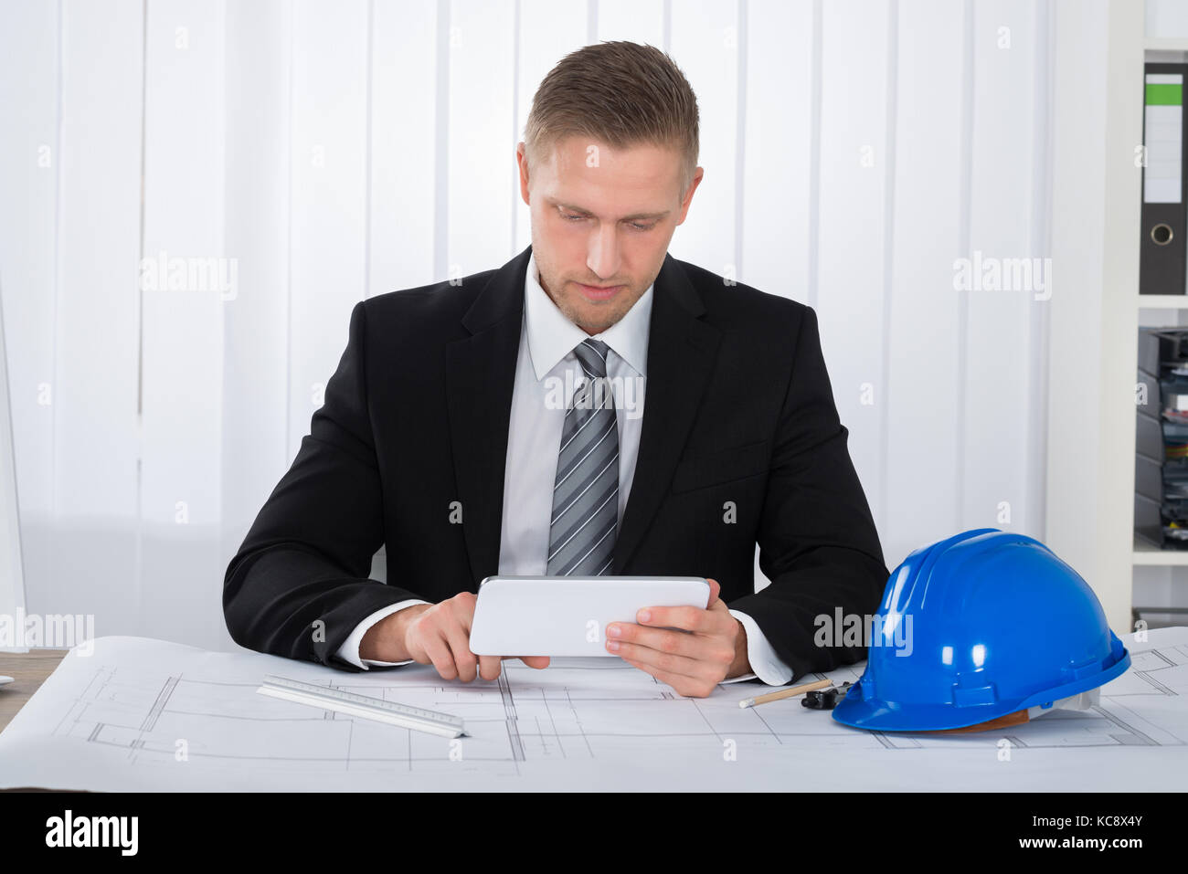 Digital scale overhead stock photos digital scale overhead stock close up of young male architecture using digital tablet over blueprint in office stock malvernweather Gallery
