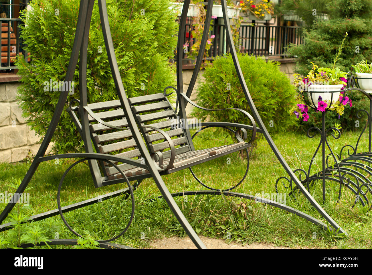 metal garden bench-swing in the courtyard in front of the fence ...