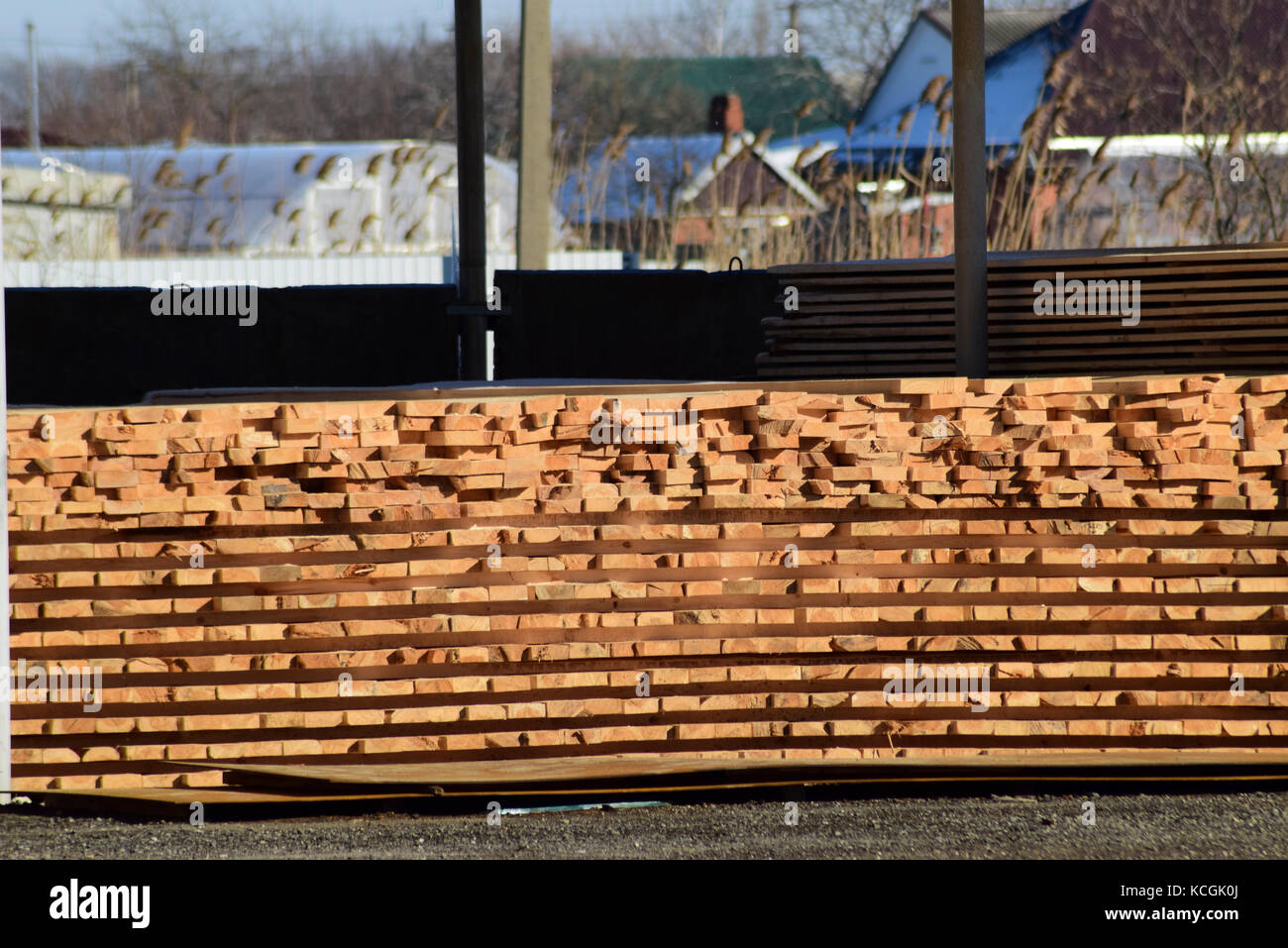 Warehouse of building materials wood planks stacked under a canopy & Warehouse of building materials wood planks stacked under a ...