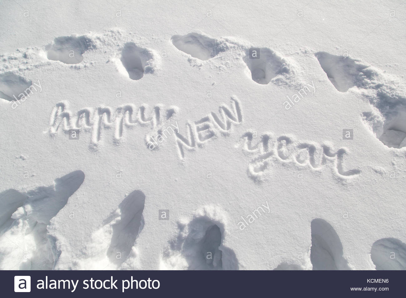 happy new year handwritten message on the deep snow with shoe prints at sunny day lovely snowy happy new year greeting card