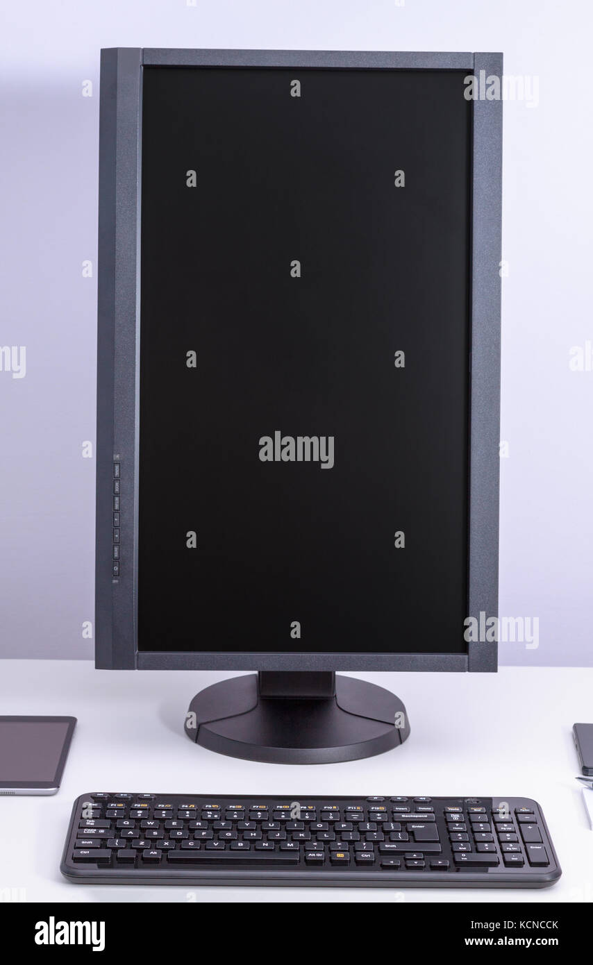 black blank pc monitor turned vertical and keyboard on desk stock