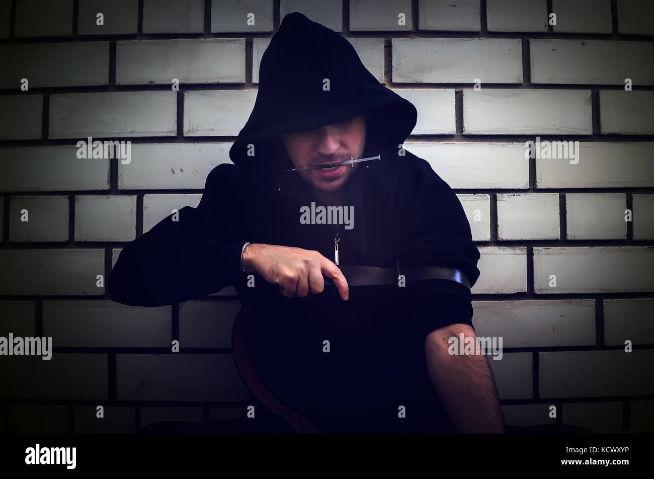 Addict With Syringe Wants To Do An Injection In A Vein On A Background Of A  White Brick Wall In An Old Dirty Crack House. The Concept Of Addiction