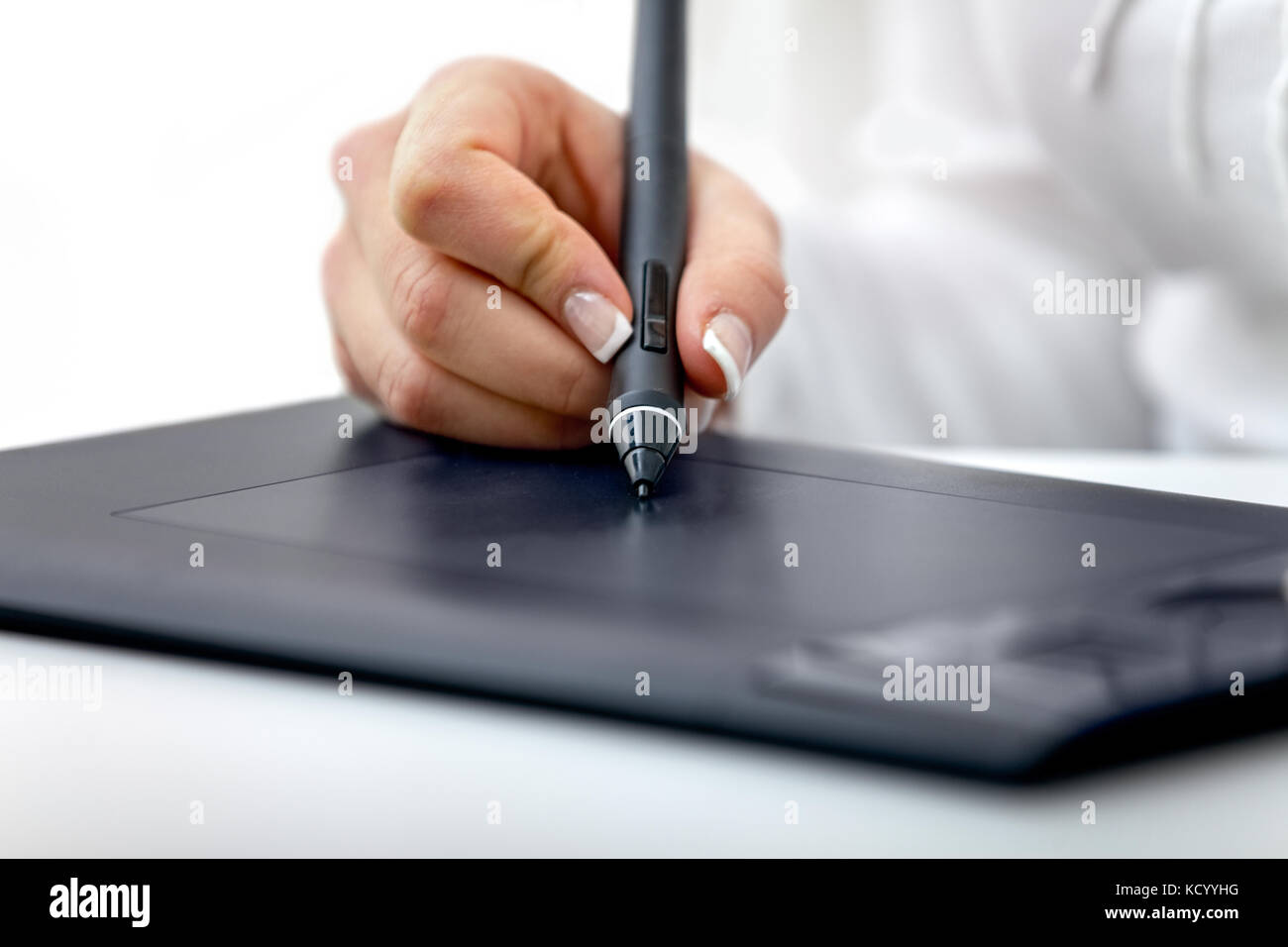 digital graphics tablet and a hand hold a stylus used for graphic