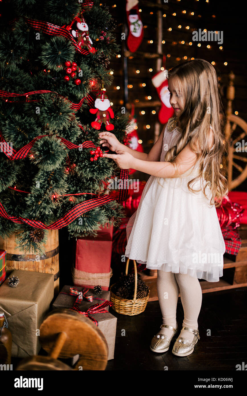 Baby girl 4-5 year old posing in room over christmas tree with Stock ...