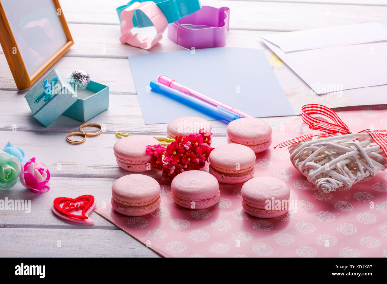 Pink heart shaped macaroons and wedding rings with postcard. place ...