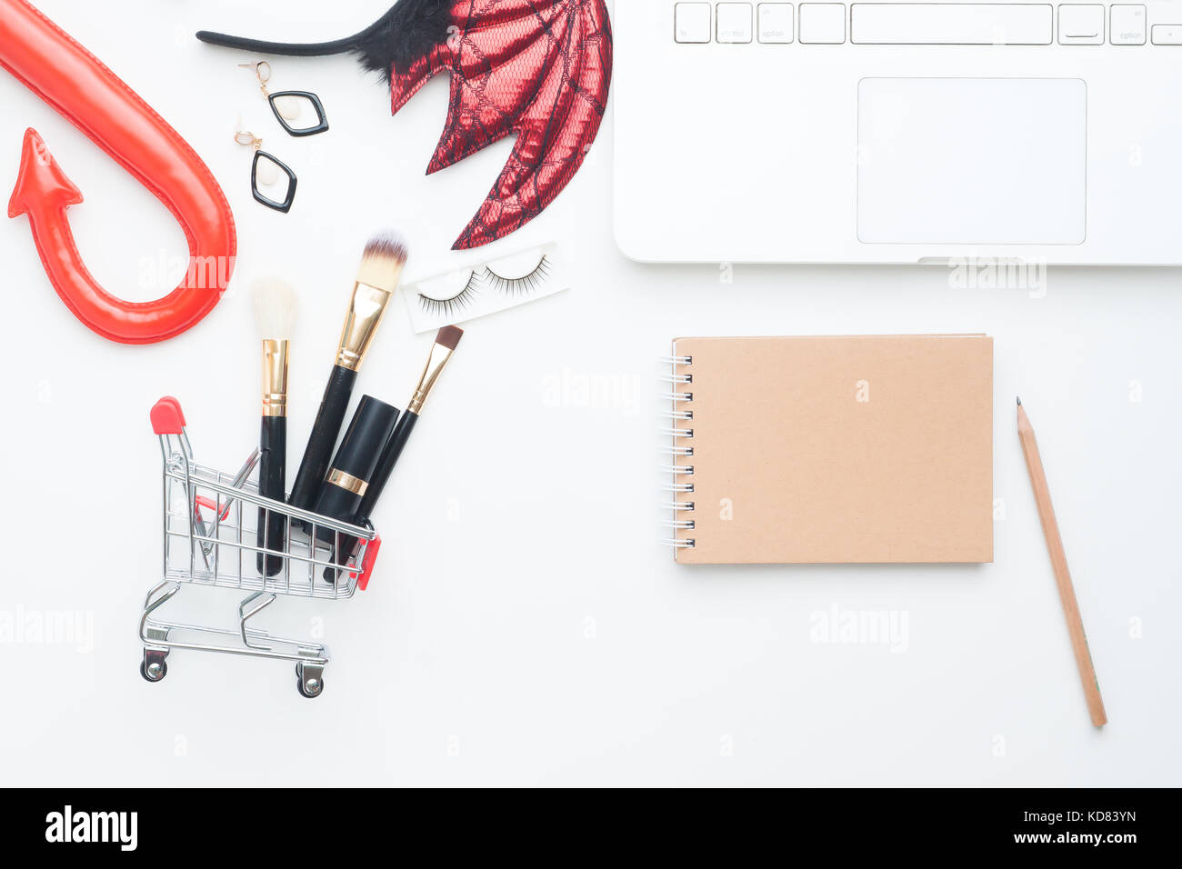 beauty items in shopping cart with halloween costume laptop computer and notebook with copy space online shopping and halloween concept