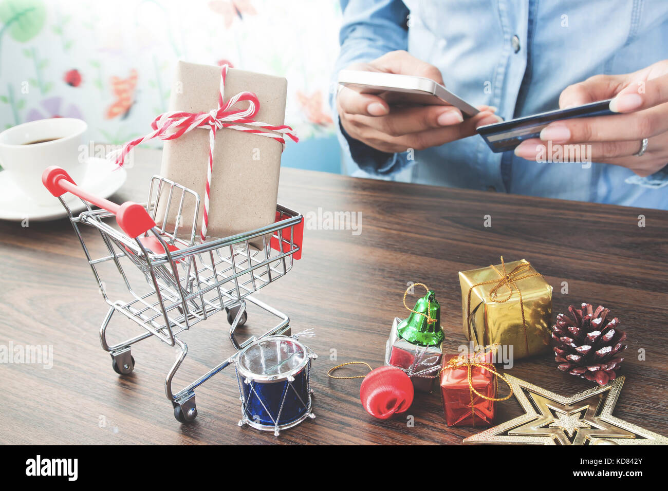 Shopping cart and gift boxes with hands holding credit card and shopping cart and gift boxes with hands holding credit card and using mobile phone online shopping for christmas negle Choice Image