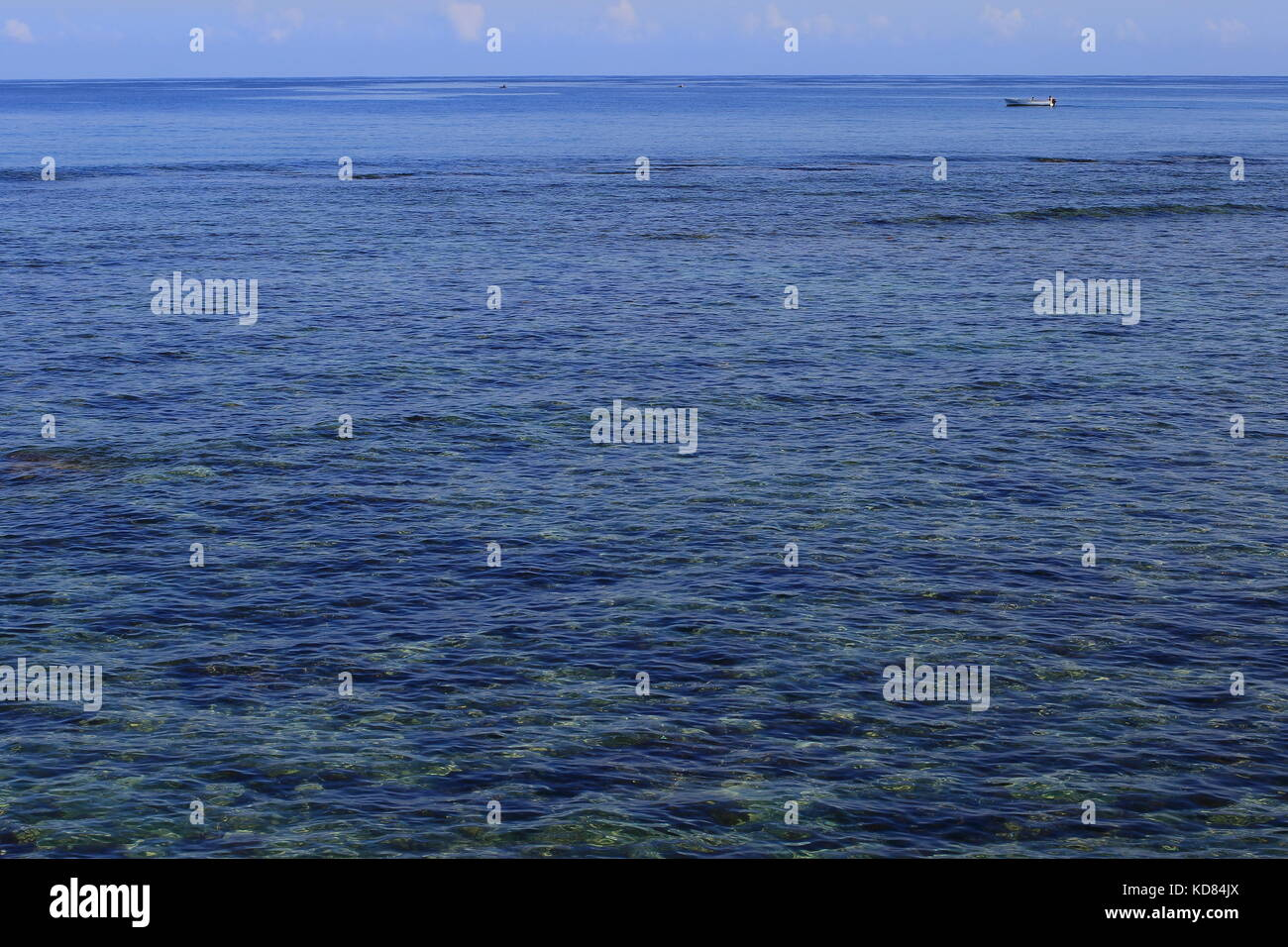 A Small White Boat Adrift In Big Blue Ocean Landscape Format With Copy Space