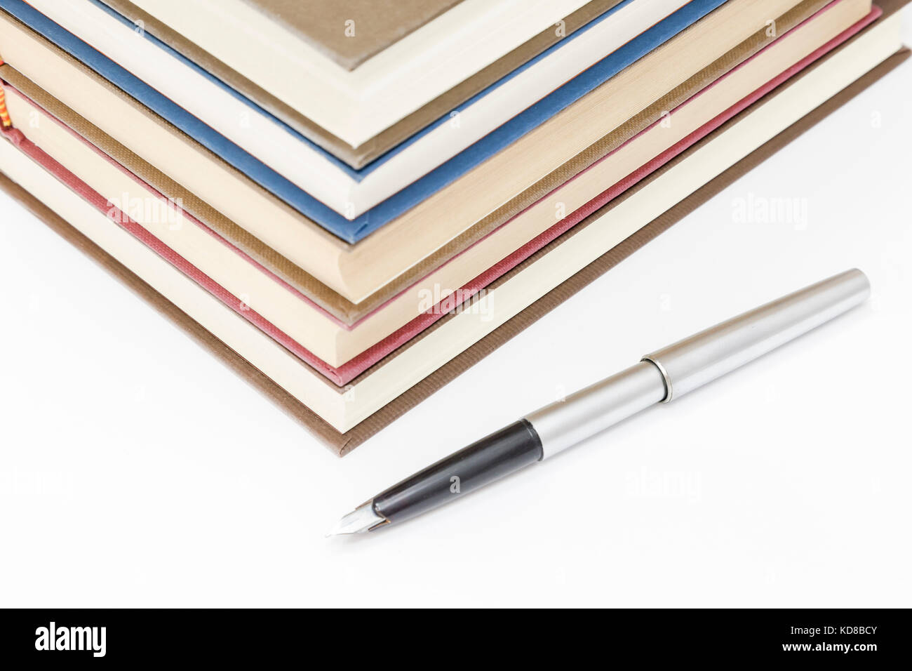 pile of old books of different colors with a pen Stock Photo ...