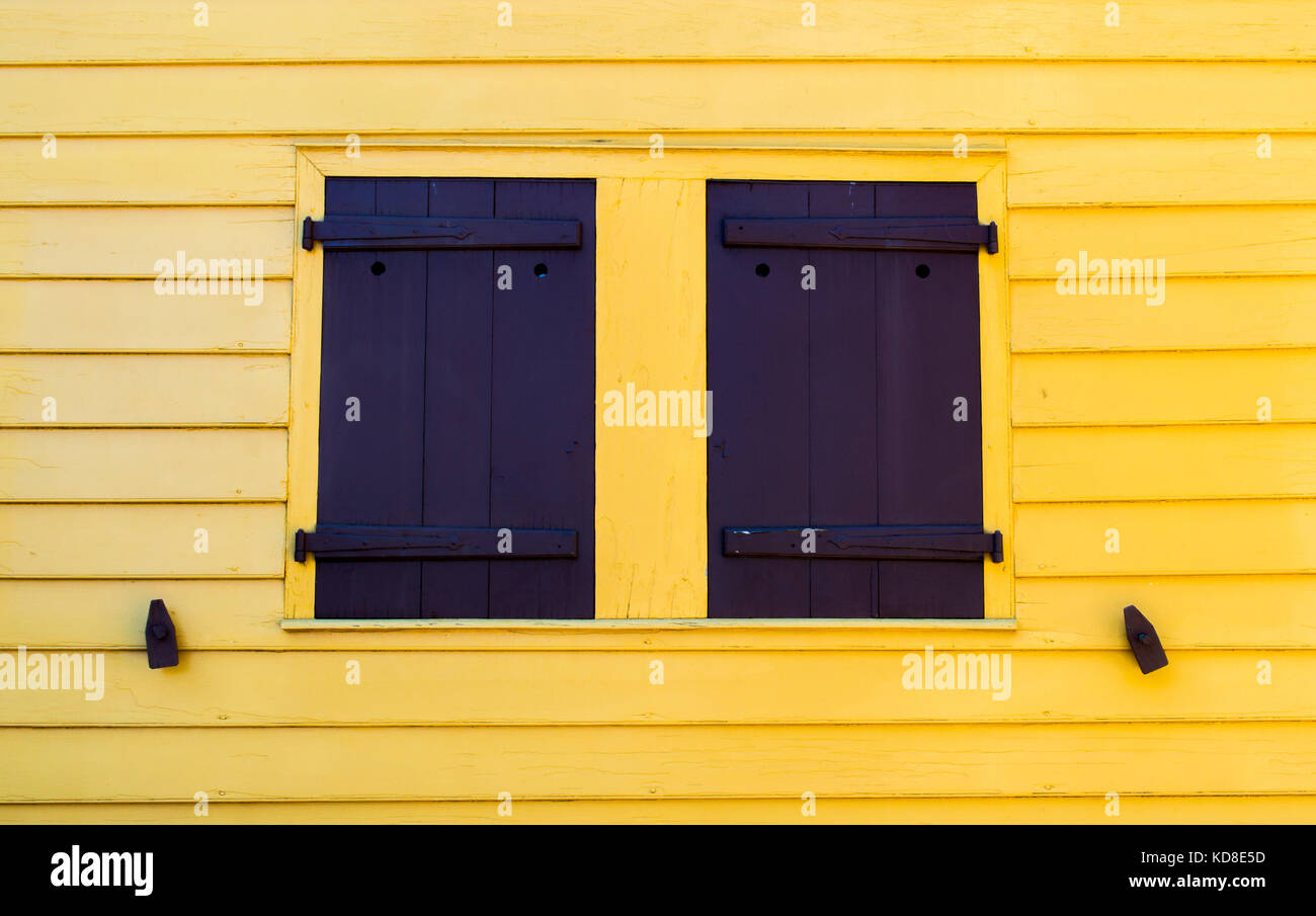 bright yellow wall with vintage black shutters and shutter dogs on ...