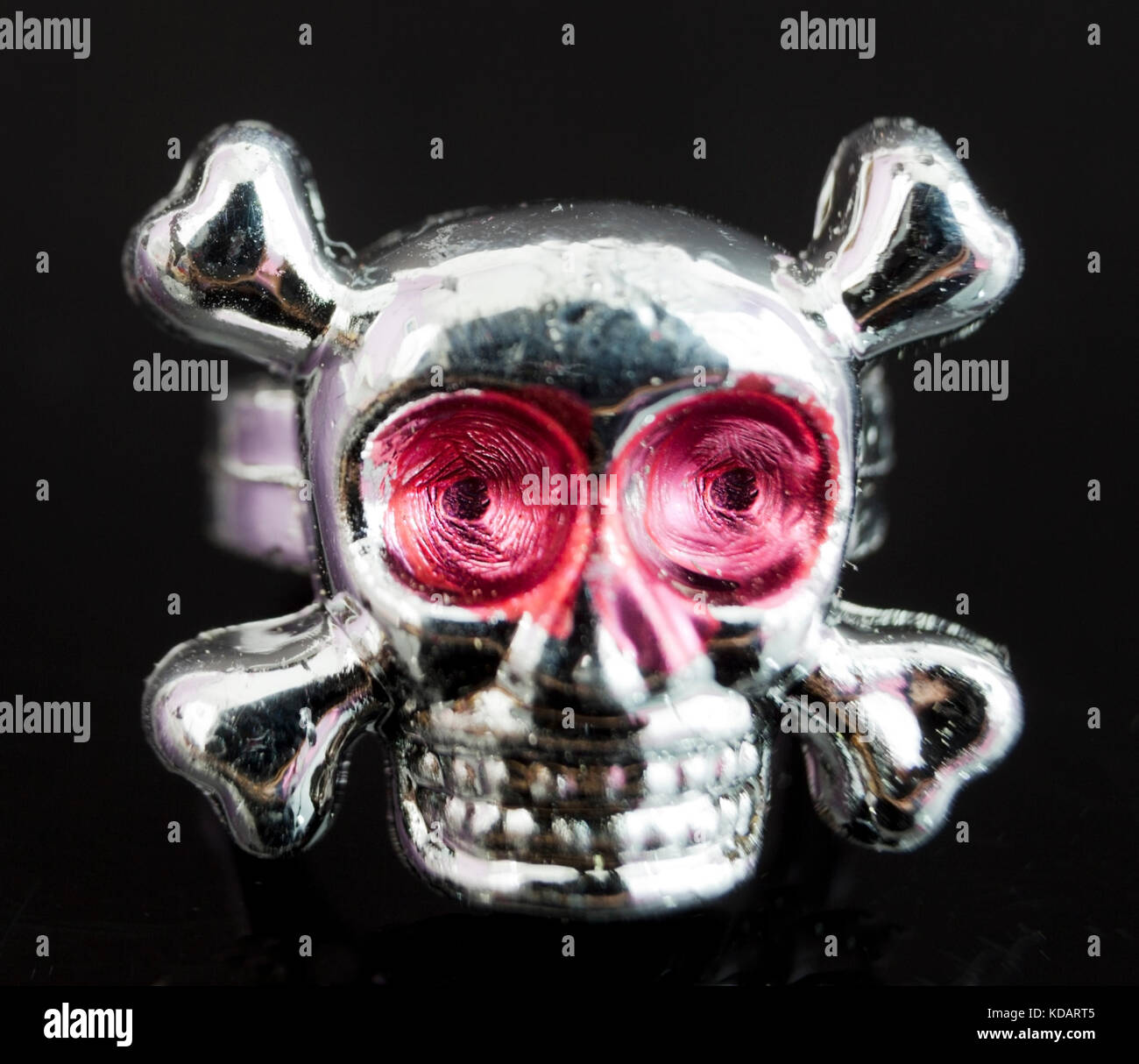 Close Up Of Toy Plastic Silver Skull And Crossbones Ring On Black Background
