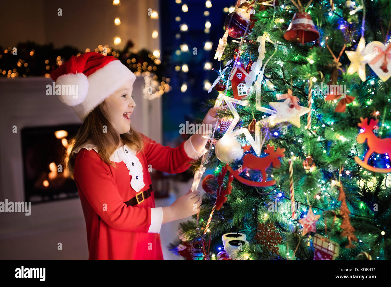 Child at Christmas tree and fireplace on Xmas eve. Family with kids ...