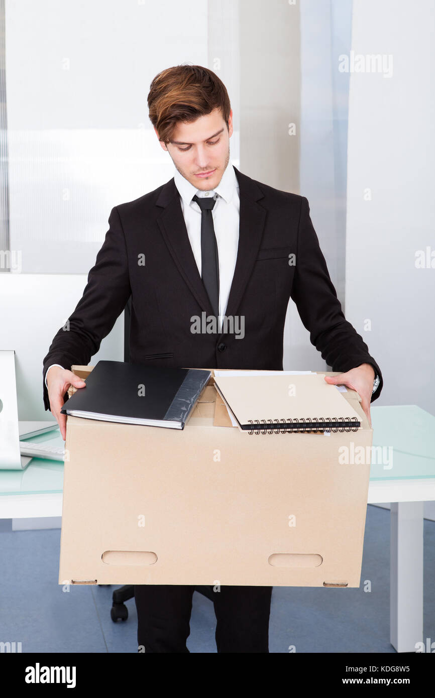 portrait of a young businessman carrying box at his workplace stock
