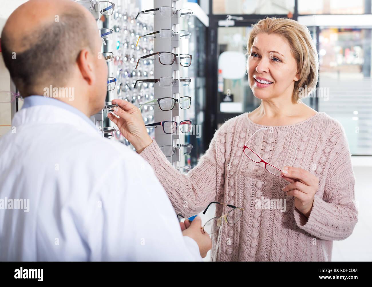 Senior optician offering glasses frames to positive elderly woman ...