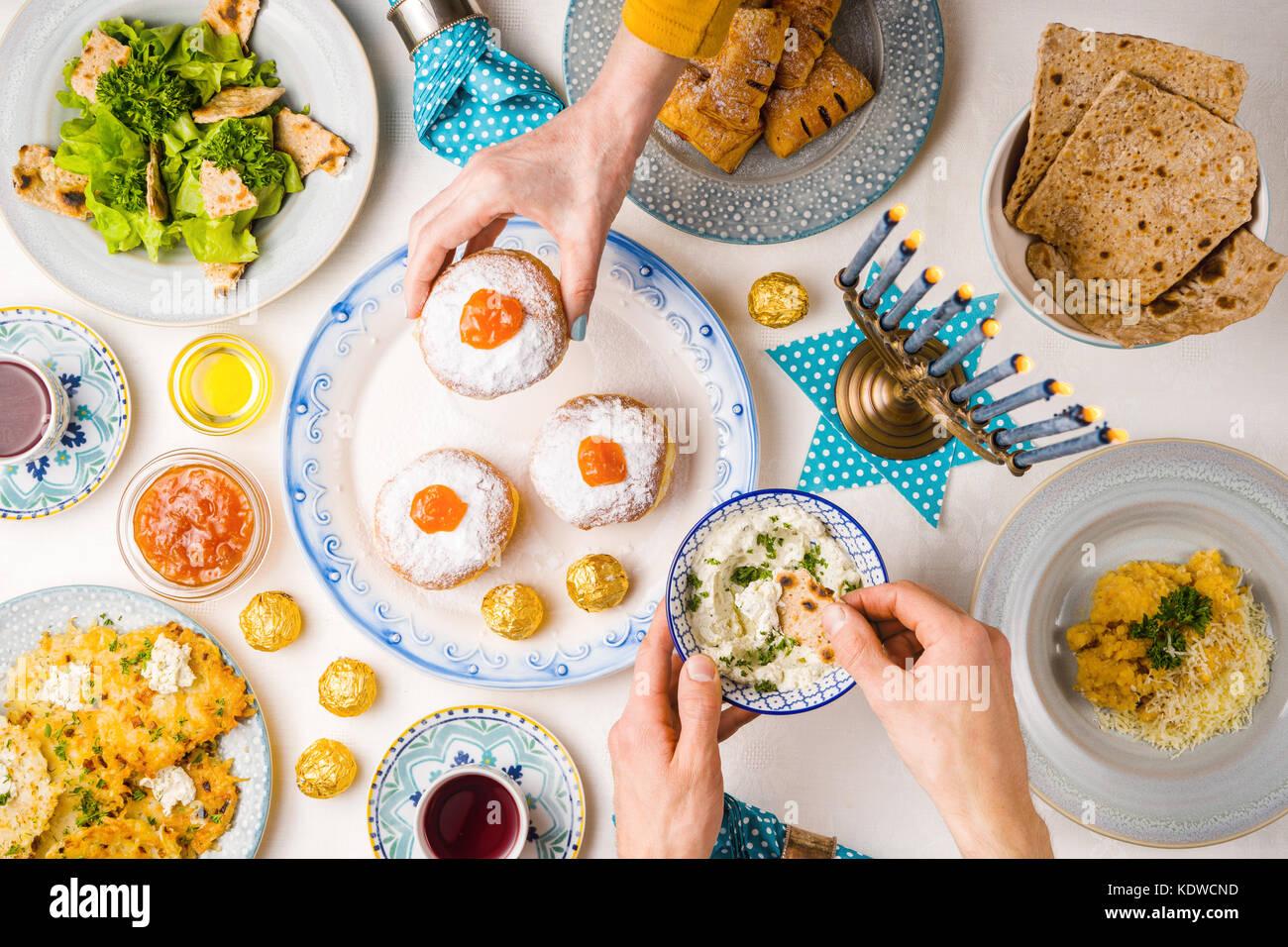 Festive feast on Hanukkah table setting hands over table horizontal & Festive feast on Hanukkah table setting hands over table ...