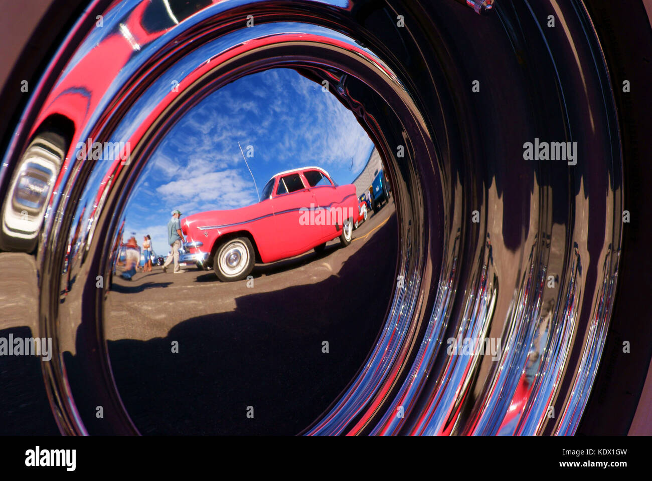 pink car reflection in hubcap stock image