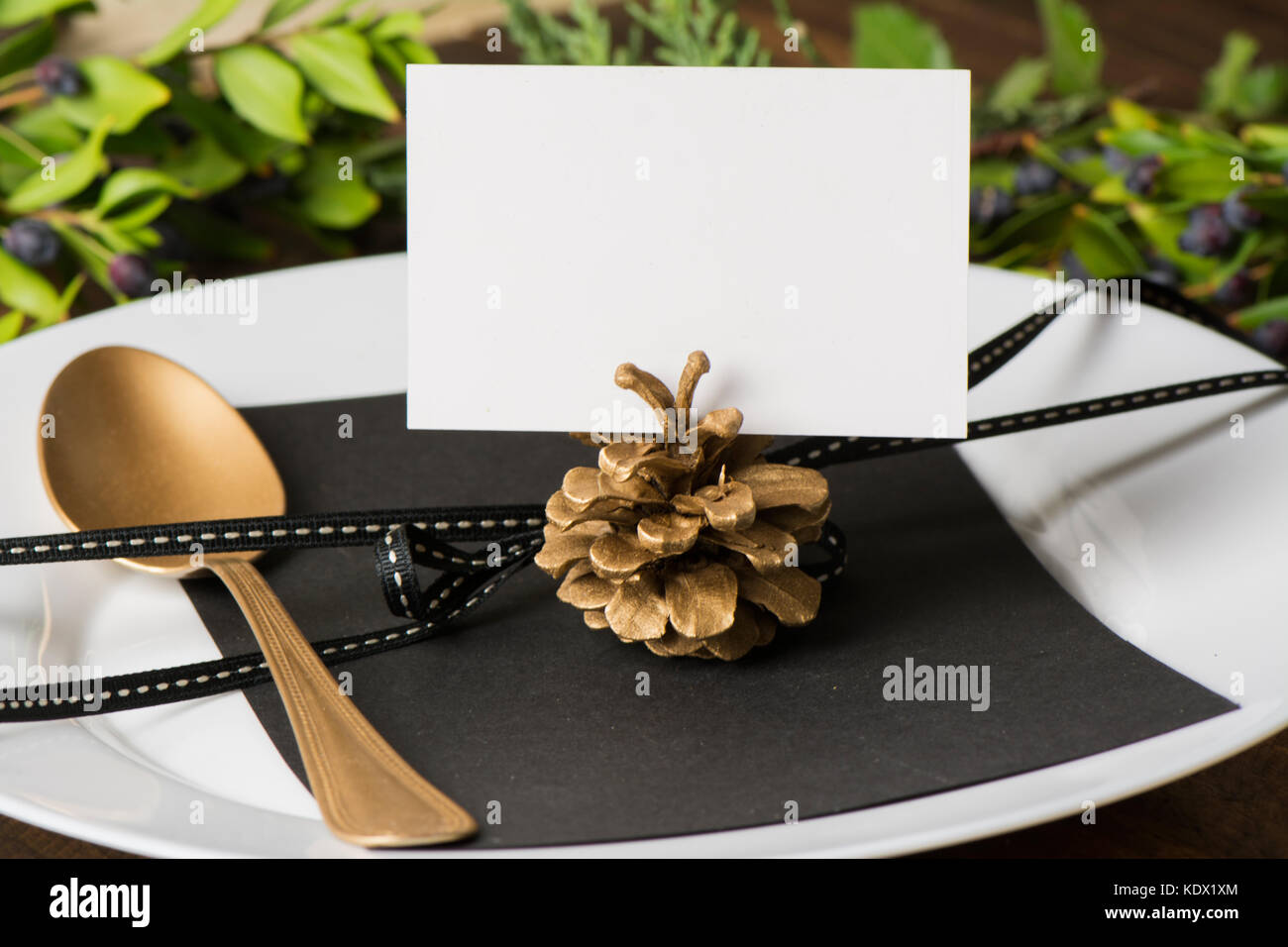 Christmas name card in the table setting, gold spoon and empty card ...