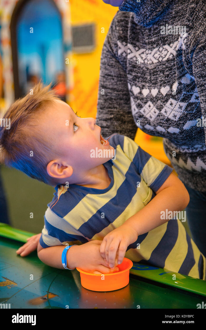 Happy Child Playing Table Air Hockey With His Grandmother In Entertainment  Center   Stock Image