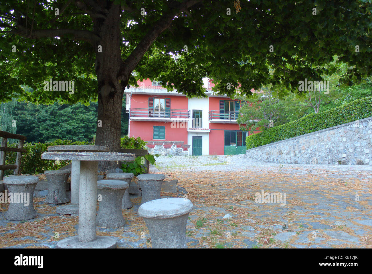 Pink Building In The Woods With A Stone Picnic Table In Foreground - Stone picnic table