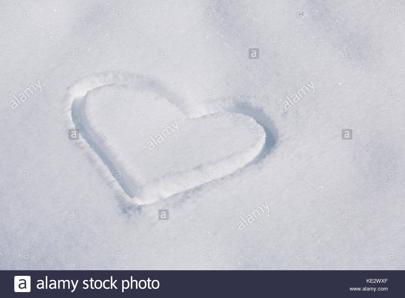 Heart symbol handwritten in the fresh snow valentines day and heart symbol handwritten in the fresh snow valentines day and christmas background with place for message biocorpaavc