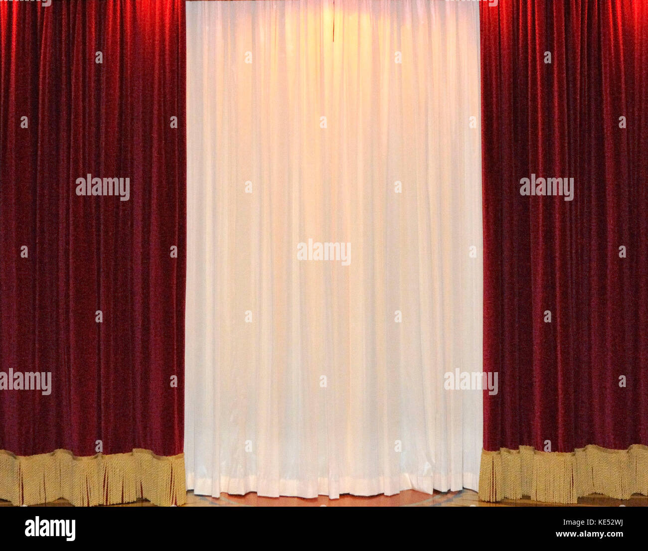 Red velvet window curtains - White And Red Velvet Curtains Cover A Cinema Screen With Pink Columns At Both Sides