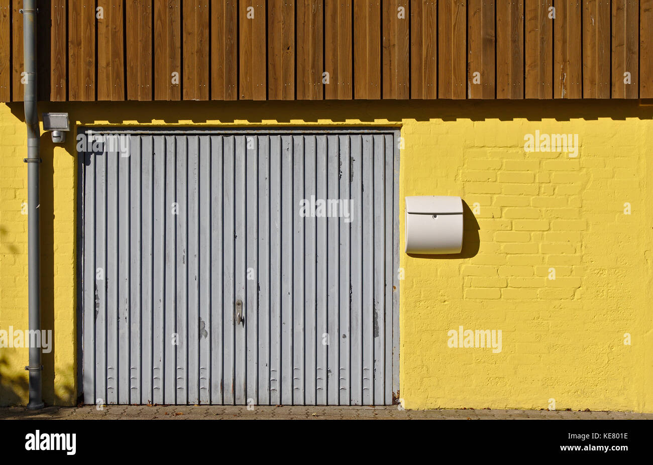Yellow brick wall with garage door mail box downspout and brown wooden paneling on