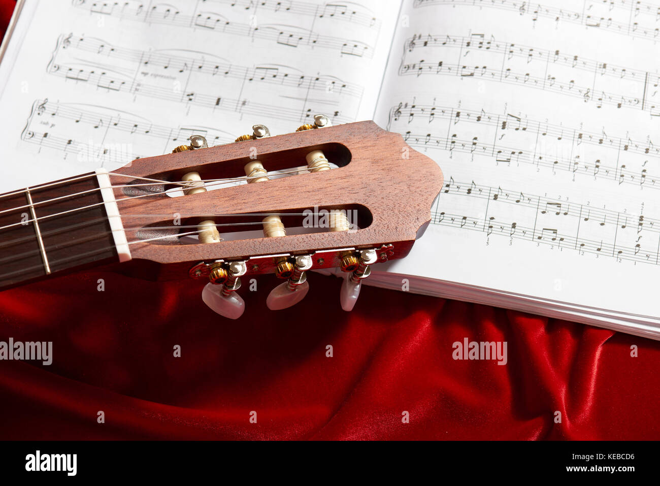 Acoustic Guitar And Music Notes On Red Velvet Fabric Close View Of