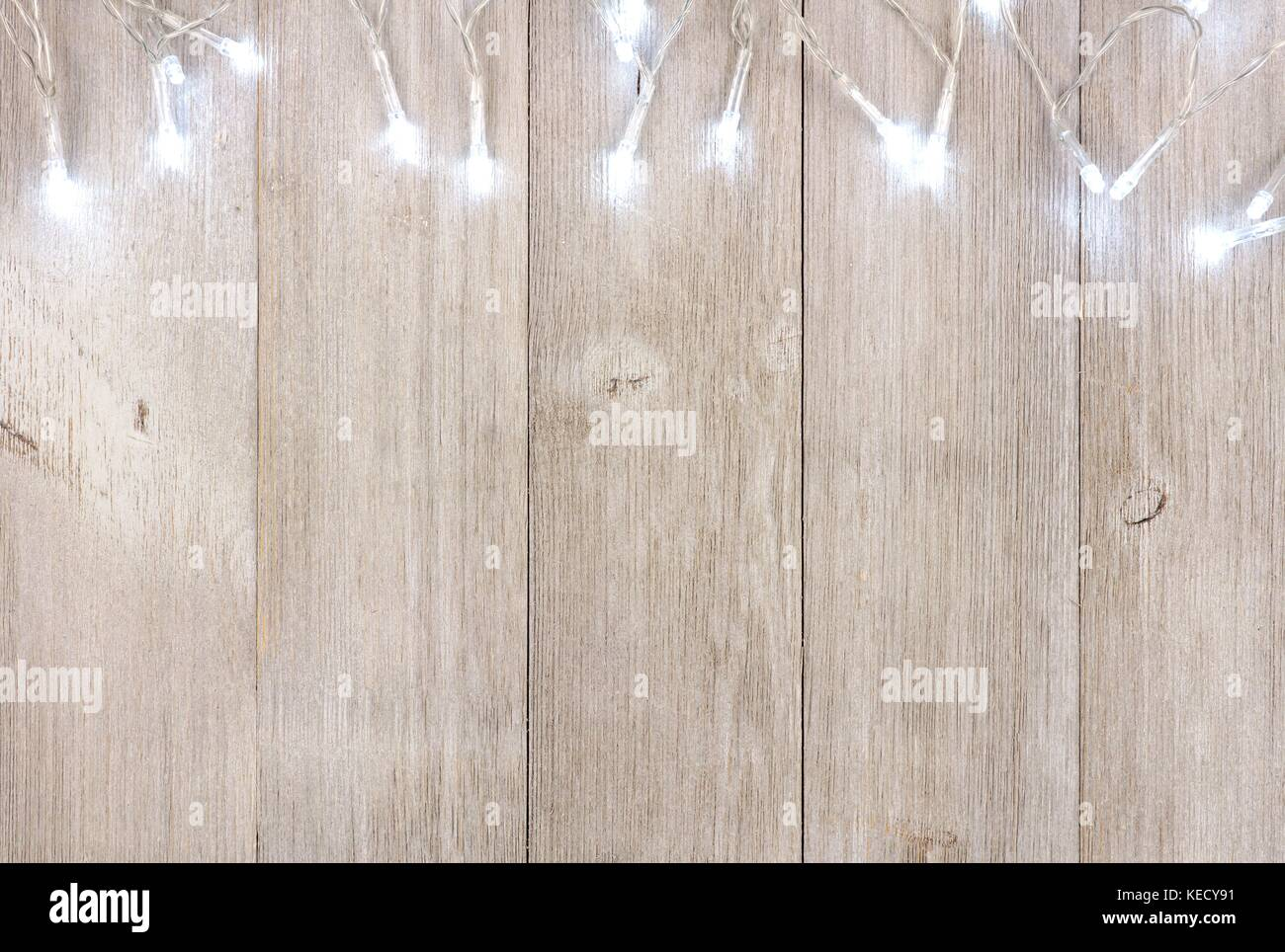 White Christmas Lights Top Border Above View On A Light Gray Wood Background