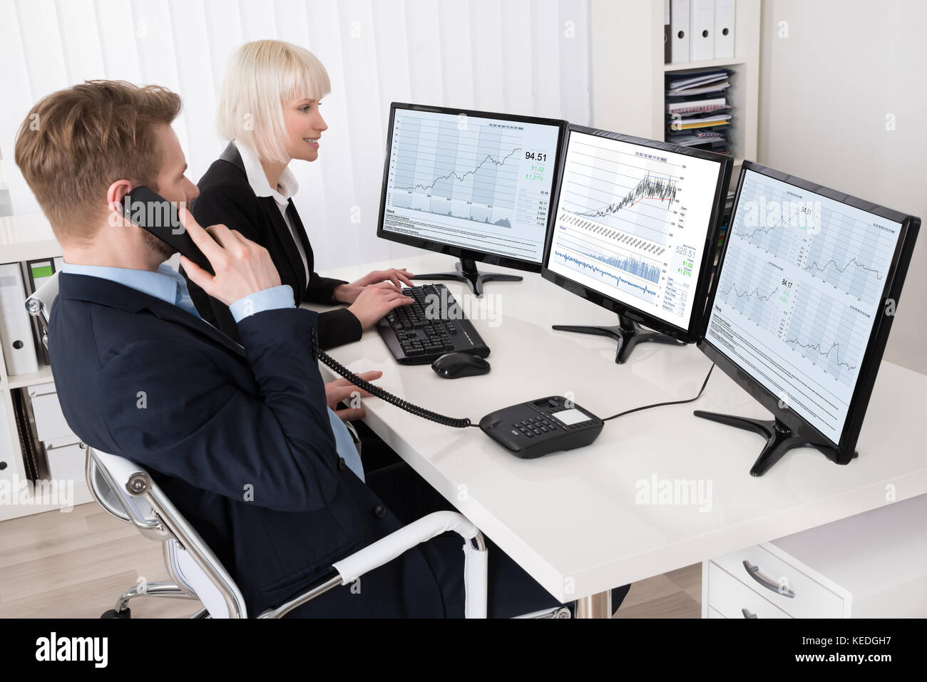 Two businesspeople analyzing stock charts on multiple computer stock two businesspeople analyzing stock charts on multiple computer screens geenschuldenfo Image collections