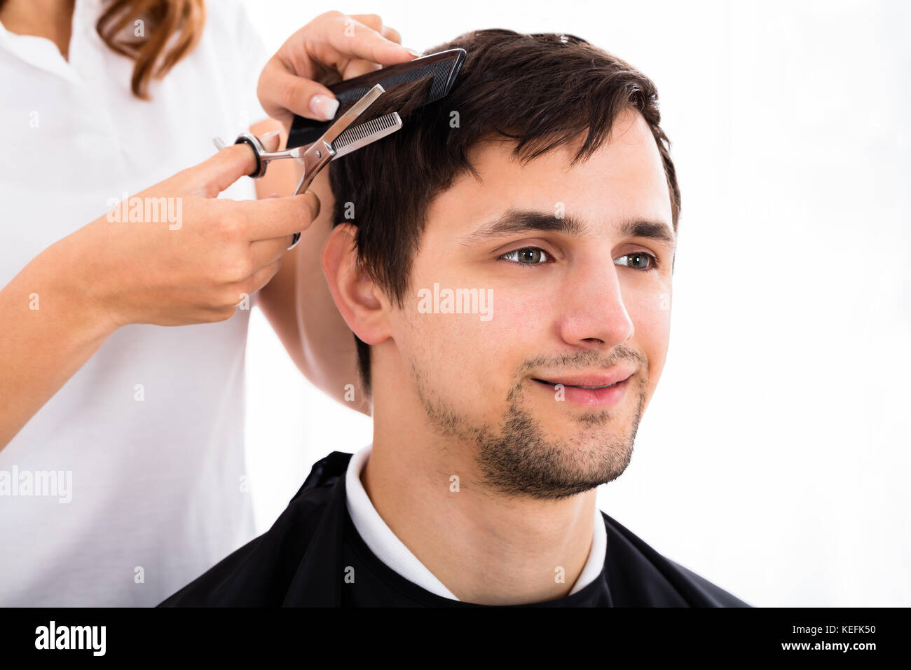 Happy Young Man Getting Haircut From Hairdresser Stock Photo