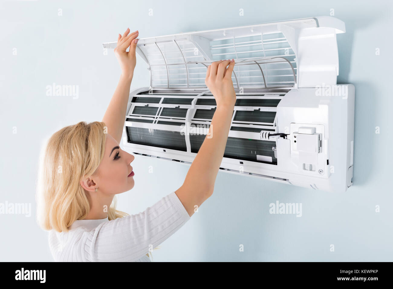 a young woman cleaning air conditioning system at home stock photo