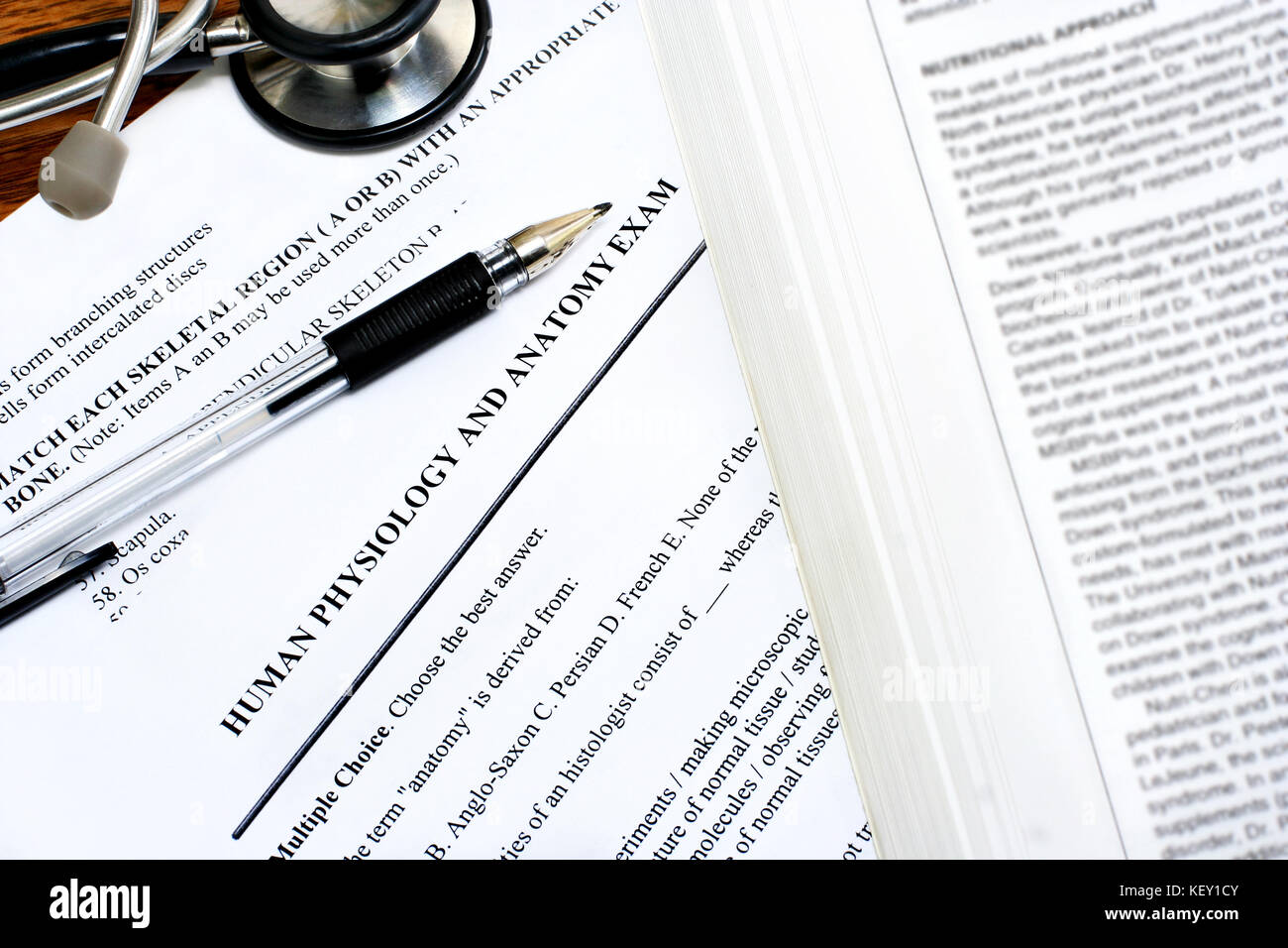 Medical exam papers on a desk with a pen, part of a stethoscope and ...