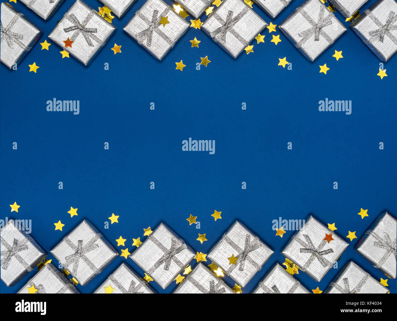border of silver shiny gifts and golden stars on blue background new years and christmas decorations group of bright gift boxes view from above