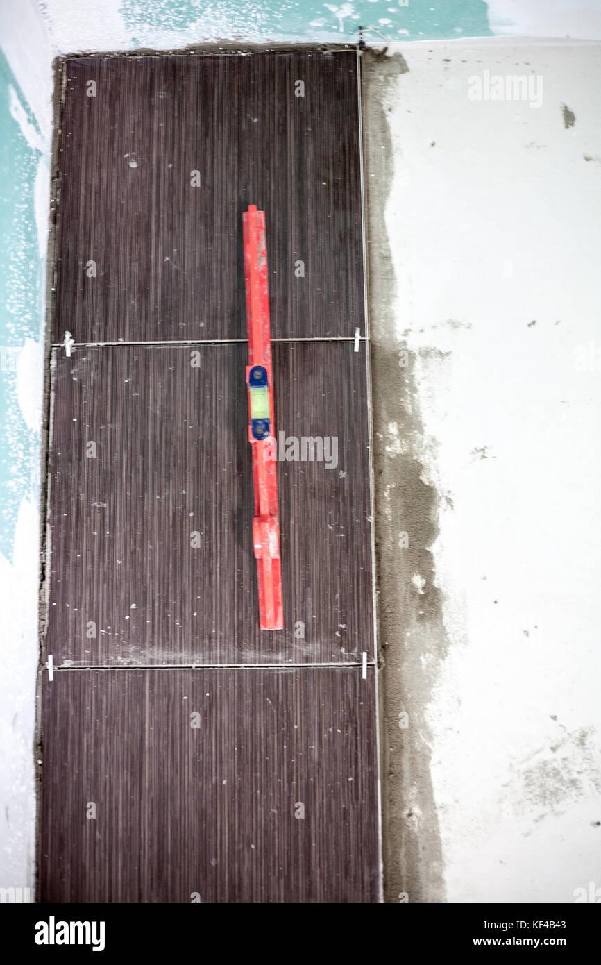 Installing ceramic floor tiles measuring and cutting the pieces installing ceramic floor tiles measuring and cutting the pieces closeup dailygadgetfo Gallery