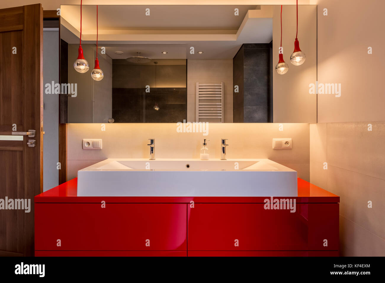 . Modern bathroom with double basin  red cabinet and big mirror Stock