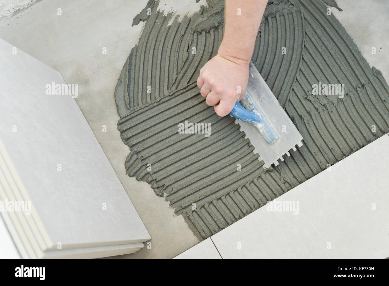 Laying ceramic tiles troweling mortar onto a concrete floor in laying ceramic tiles troweling mortar onto a concrete floor in preparation for laying white floor tile dailygadgetfo Choice Image