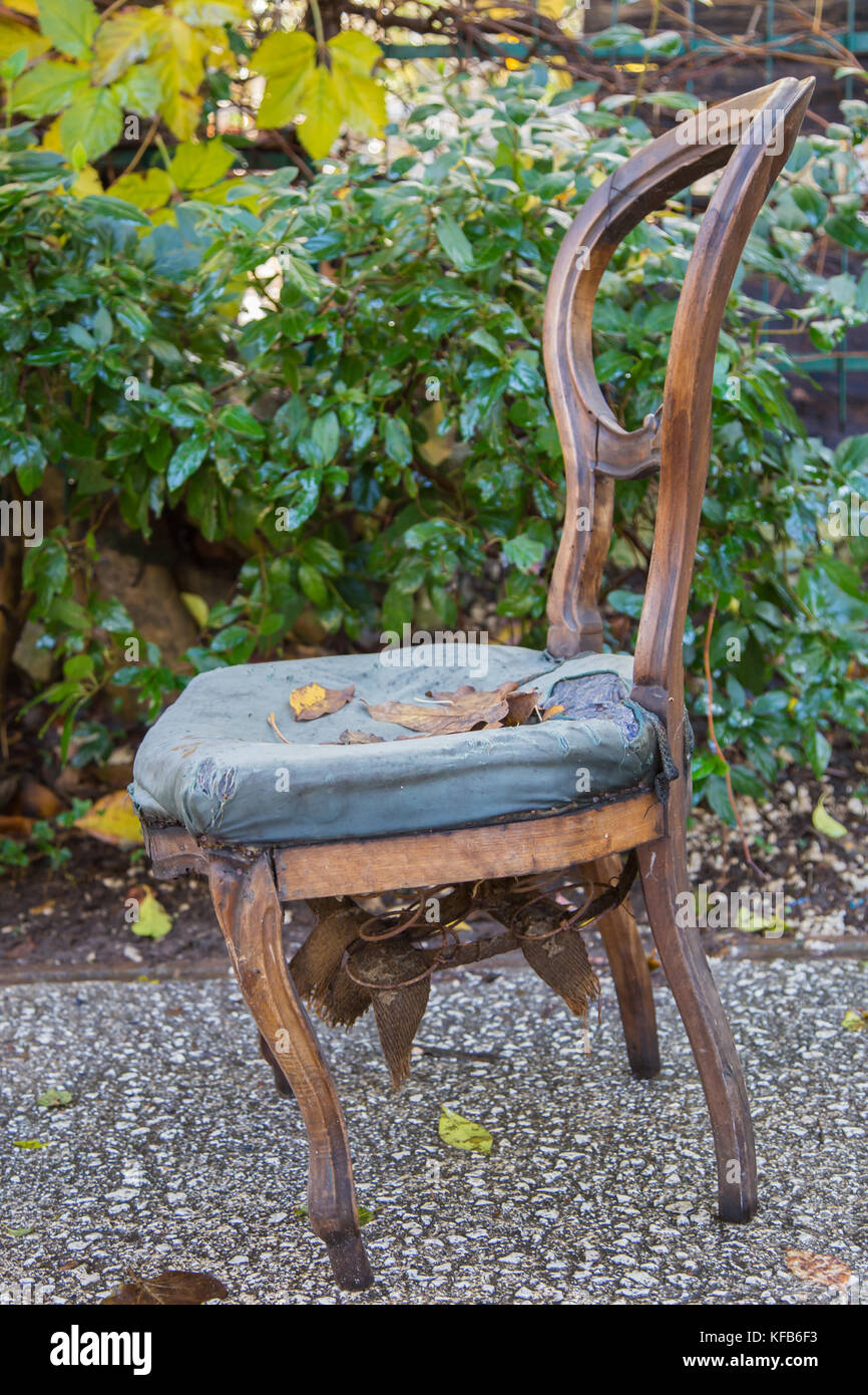 Old Wooden Chair With Torn Cloth And Rusty Springs Coming Out From Under