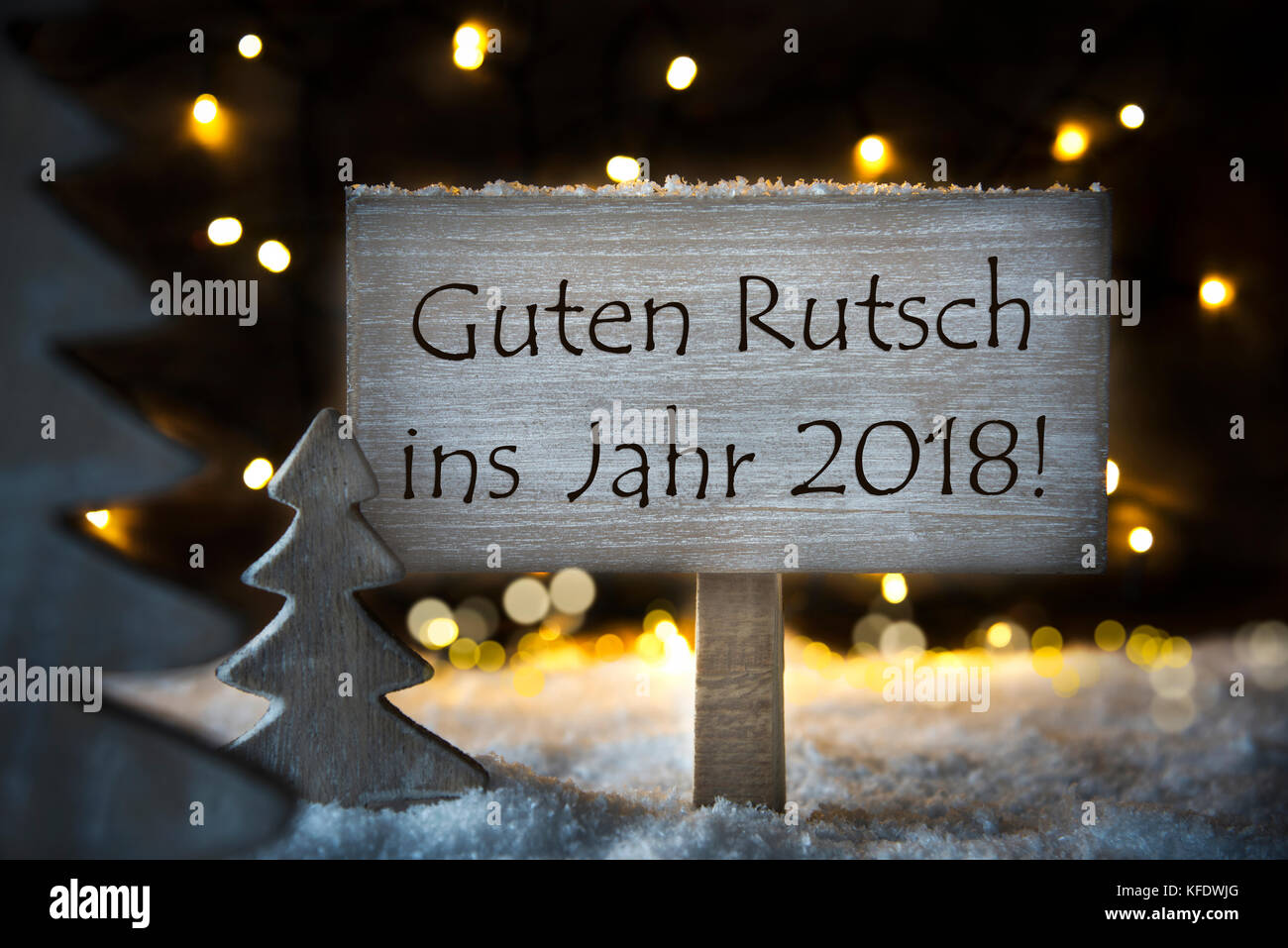 sign with german text guten rutsch 2018 means happy new year 2018 white christmas tree with snow and magic glowing lights in backround card for seas