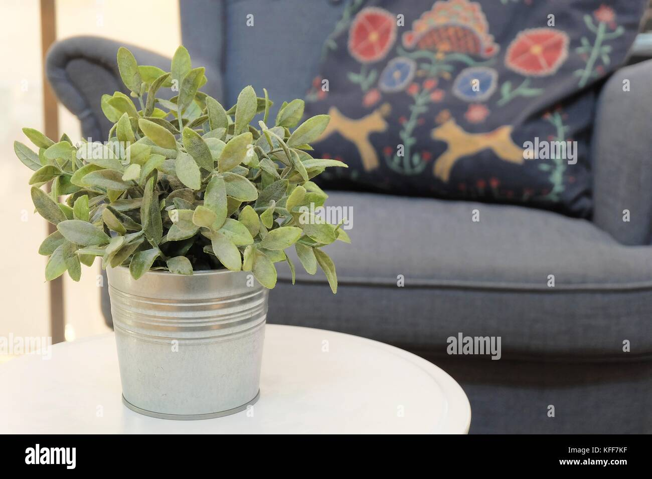 Artificial Green Plants In White Metal Flower Pot In A Living Room